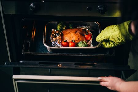 Photo pour Cooking healthy food. Woman taking baked chicken breasts from oven. Fat- free, no fry meals - image libre de droit