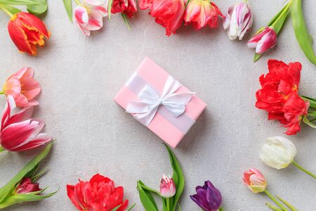 Photo for Spring floral design greeting card. Multicolored tulips border and gift box on grey stone surface. Copy space - Royalty Free Image