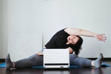 Foto de Obese woman doing stretching exercises at home - Imagen libre de derechos