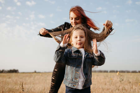 Photo pour Mother and daughter. Motherhood, family concept. Loving mom walking outdoors spending time having fun together with her little daughter - image libre de droit