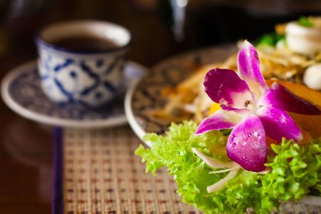 Beautifully served thai noodles with orchid and a cup of tea, shallow DOF, focus on the flower