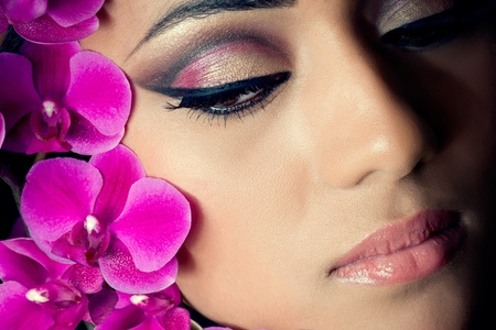 Closeup shot of a beautiful young woman's face with purple orchid flowersの写真素材