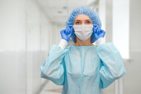 Photo pour Portrait of doctor in scrubs. A female doctor in a protective cap and face mask in safety measures against the coronavirus. - image libre de droit