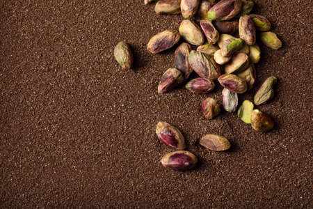 Photo for Pistachio nuts on brown textured sand  background - Royalty Free Image