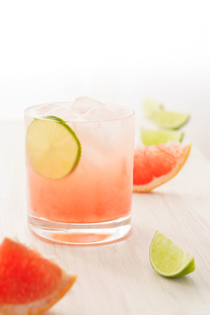 Photo pour Paloma cocktail served with grapefruit and lime slices. White wooden background, high resolution - image libre de droit