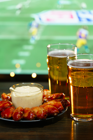 Photo pour Hot barbecue chicken wings with 2 beer glasses on a dark wooden table served with honey mustard sauce. Football on a background, high resolution - image libre de droit