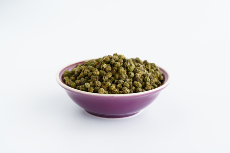 Dried green peppercorns in a violet bowl. White background, high resolution