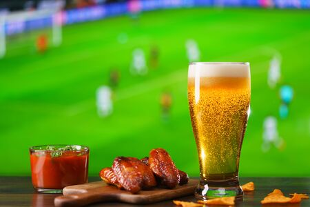 Photo pour Spicy barbecue chicken wings, tomato salsa, nachos and beer on dark wooden bar table. Football on background, high resolution - image libre de droit