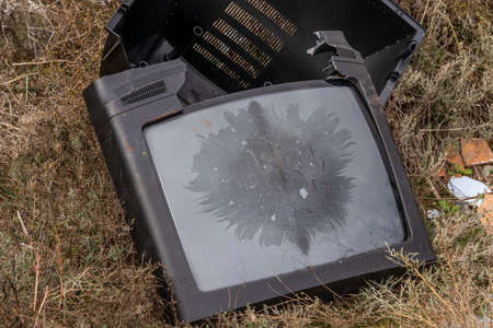Photo pour Television set polluting and littering the countryside with residues - image libre de droit