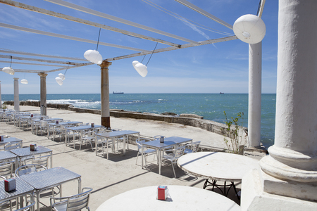 Terrace beside the sea with pergola, columns and paper lamps a windy day