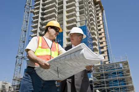 Building developer and contractor discuss progress on a hirise construction project at the job site