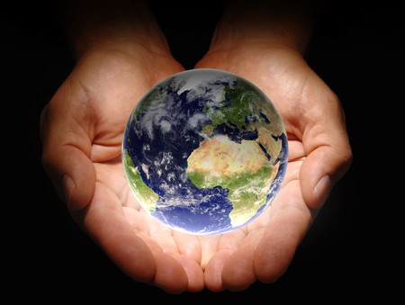 Hands holding the earth on a black background