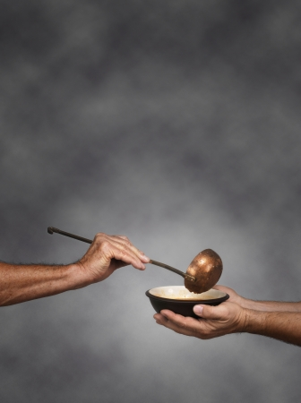 Vertical composition of a man holding a bowl in both hands, receiving a serving of soup from another man holding a soup ladle