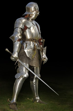 Medieval knight in shining armour of the 15th century standing outside with sword. Isolated on a dark background