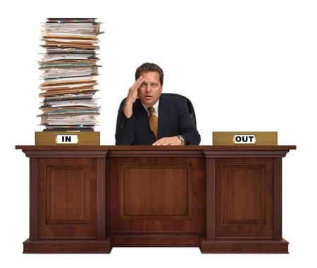 an in-box on a corporate deskwith overflowing with a mountain of paperwork  with with an overworked man behind it wearing a suit and tie on white background