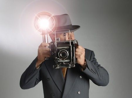 Retro 1940's stylephotographer wearing a Fedora hat and holding a vintage camera with flash bulb flashing