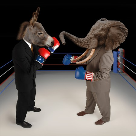US Republican and Democrat mascots represented by a donkey and an elephant face off in a boxing ring in business suits with red white and blue boxing gloves.