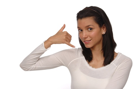 Beautiful, young woman on a white background gesturing with her hand as though it were a telephone