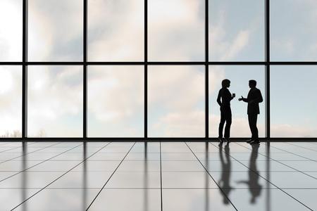 Foto de Profiles of two business people against a bank of windows in an office tower - Imagen libre de derechos