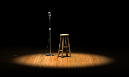 Microphone stand and wooden stool under a spotlight on a stage