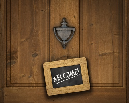 Small chalkboard hanging on a door underneath the door knocker with the word