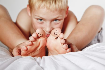Photo pour Portrait of young boy in his bed with smiley faces painted on two of his toes - image libre de droit