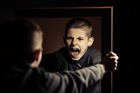 Photo pour Close up Angry Young Boy Shouting on his Own Mirror Reflection with Mouth Wide Open Against Black Background. - image libre de droit