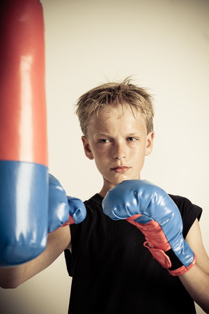 Solitary serious blond boy with spiky hair wearing black sleeveless shirt strikes red and blue punching bag with boxing gloves