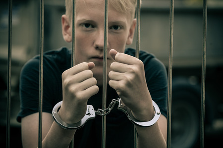 Handcuffed teenage boy behind bars in a prison cell staring intently at the camera unrepentant of his criminal behavior