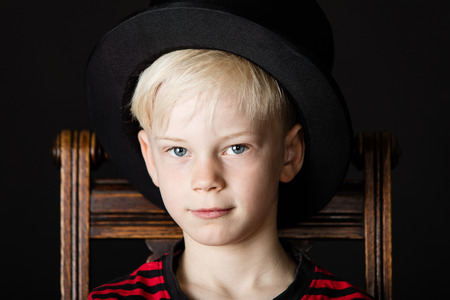 Handsome little boy wearing a black top hat as he sits on an old wooden kitchen chair looking solemnly at the camera in a close up face shot