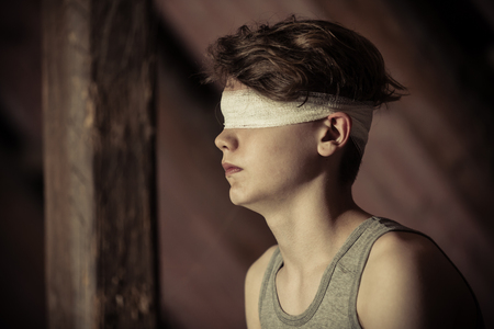 Teenage boy tied up in a blindfold sitting in an attic in the darkness in a conceptual image of abuse and hostage taking