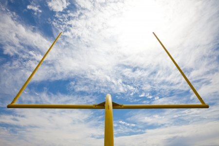 Yellow american footbal uprights against a partially cloudy sky  Viewed from below and the back of the field goal