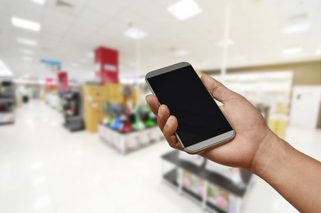 a hand holding blank screen smartphone on blurred electronics store, modern life shopping concept