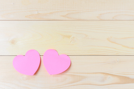 Pink sticky notes hearts shaped holes on wooden background with copy space