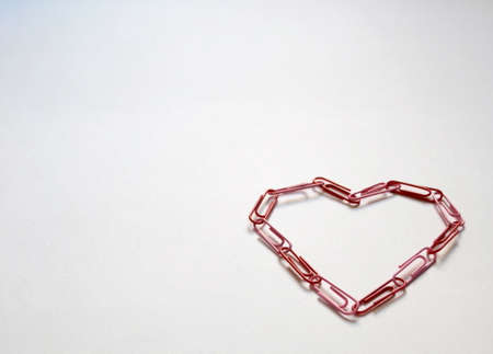 Heart made with red clips on a white paper