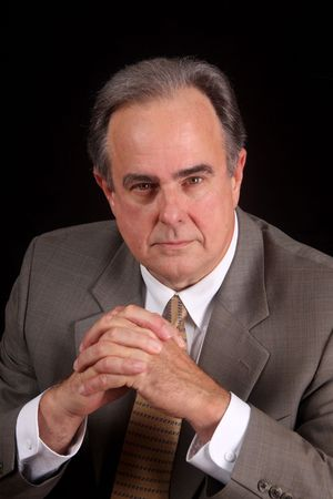 Mature businessman with a serious expression set against a black background