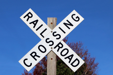 Railroad crossing sign against blue sky background