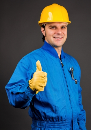 Young construction worker giving thumb up sign against gray