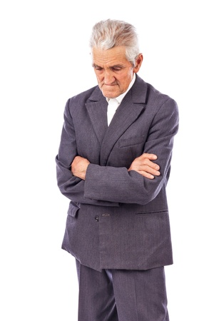 Elderly man with arms folded looking down lost in deep thought on white background