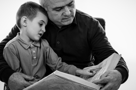 Portrait of a  man reading a story book for his grandson over white.Monochrome portrait