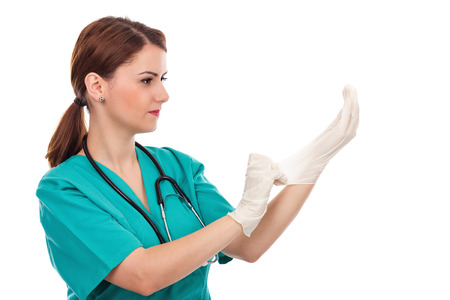 Attractive female doctor putting  sterilized surgical gloves isolated over white background