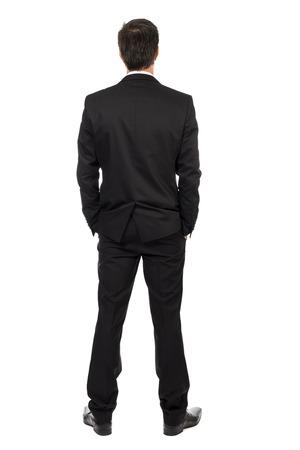 Full body portrait of young businessman, back view, with hands in pocket isolated over white backgroundの写真素材