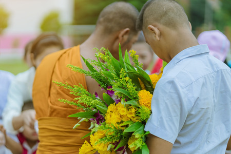 Teachers and students together make merit to give food offerings to a Buddhist monk on important religious days at school.