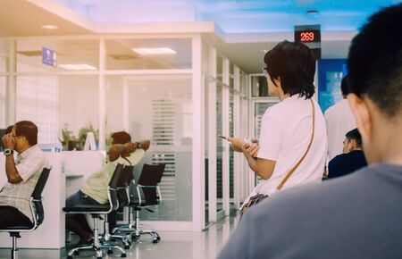 Foto per Back view of people sit and waiting in financial transactions in the bank. - Immagine Royalty Free