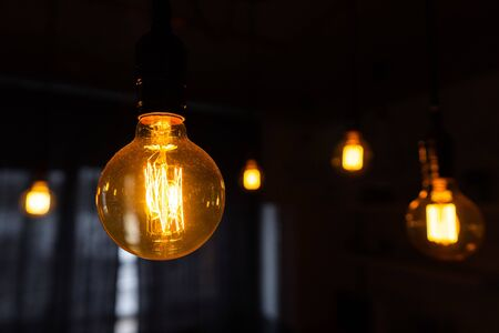 Photo for Close-up of incandescent light bulbs hanging in the dark room. Inefficient filament light bulbs waste electricity. Decorative antique edison light bulbs with straight wire. Dimmable, warm white, E27 - Royalty Free Image