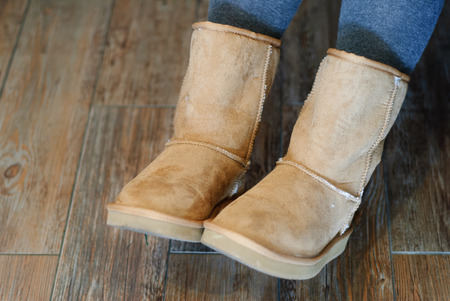 Closeup of brown Ugg boots with wooden background