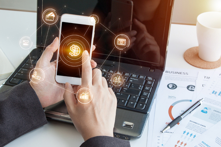 Photo pour Online banking payment communication network digital technology application development mobile smartphone sync app: Close up hand business woman/ man holding mobile phone with Mobile banking icon flow - image libre de droit