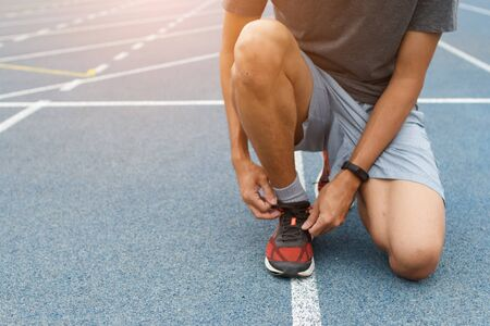 Close-up of sportsman in blue running track in stadium. He tying sneakers on running shoes before practice. Running concept.