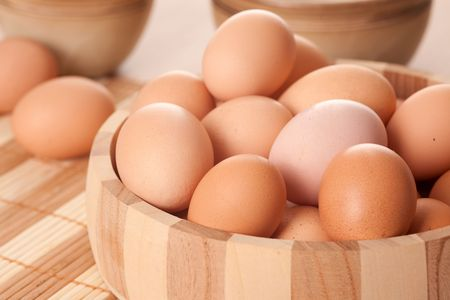 eggs in wooden bowl on table