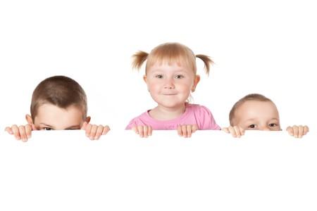studio shot of three child behind white board